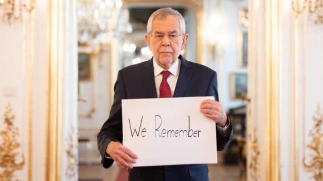 """Bundespräsident Alexander Van der Bellen mit einem Plakat mit der Aufschrift """"We Remember"""" anlässlich des Holocaust-Gedenktags."""